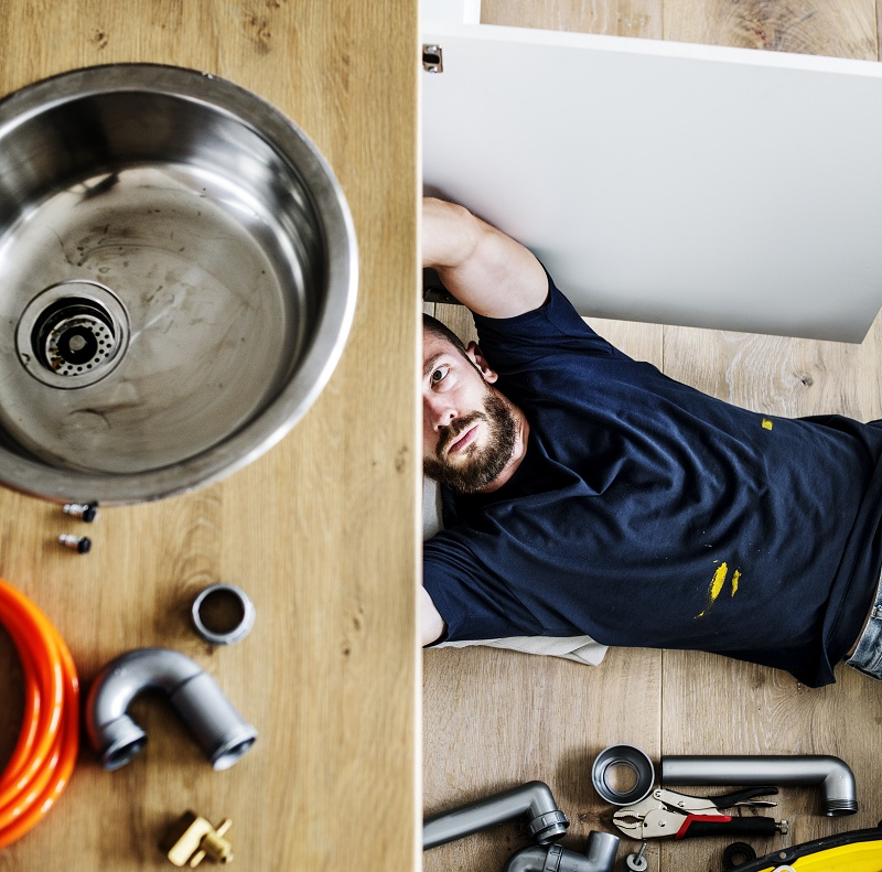 man fixing pipes under kitchen sink