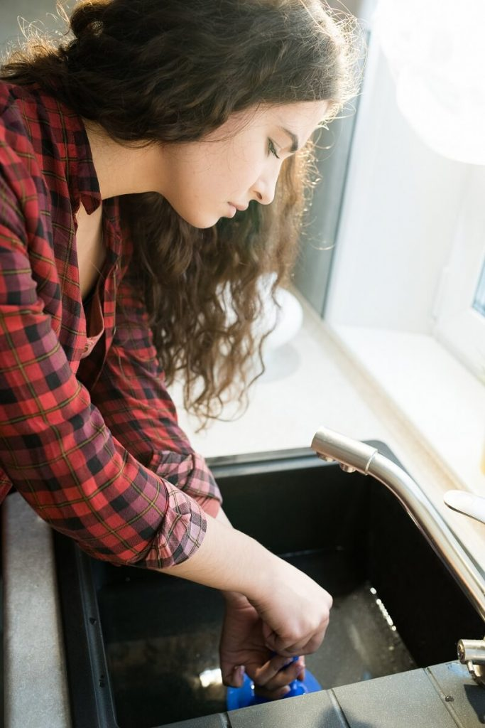 woman clearing clogged drains