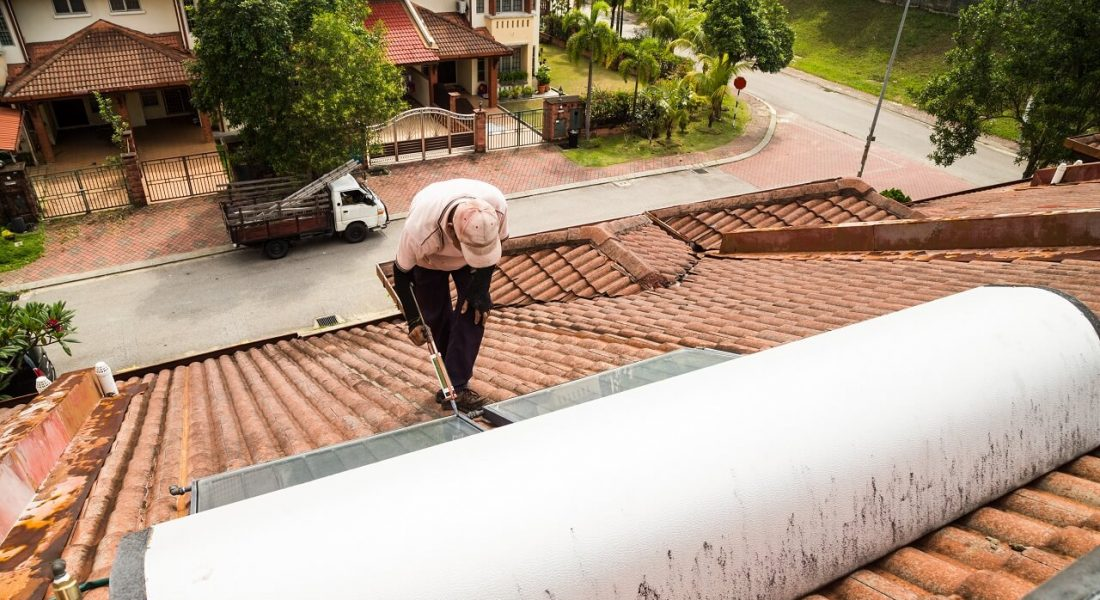 man fixing solar water heater on the roof