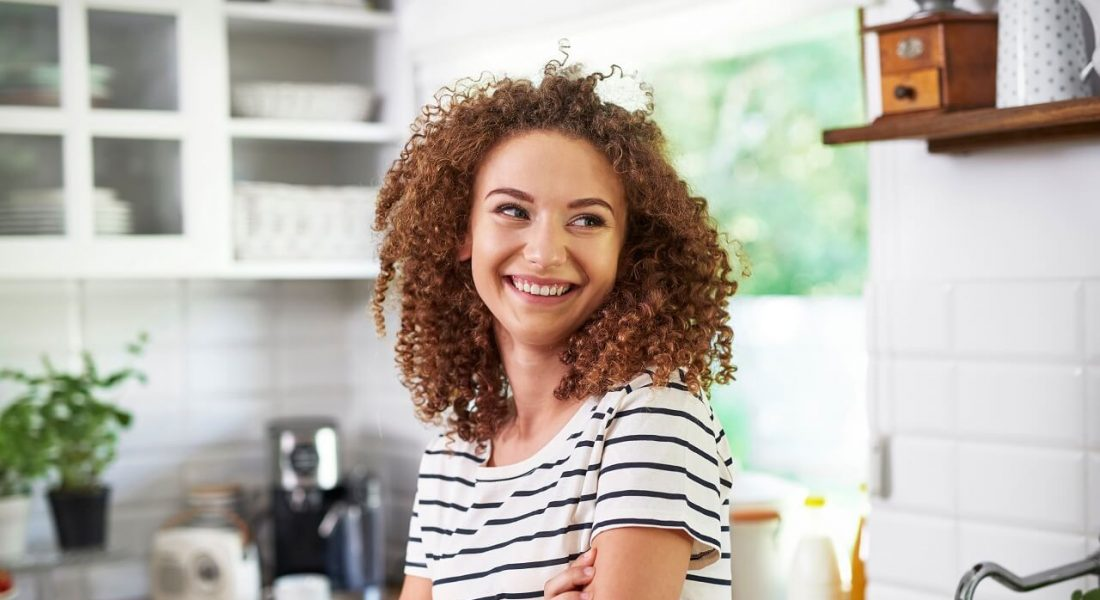 young woman in her small kitchen smiling